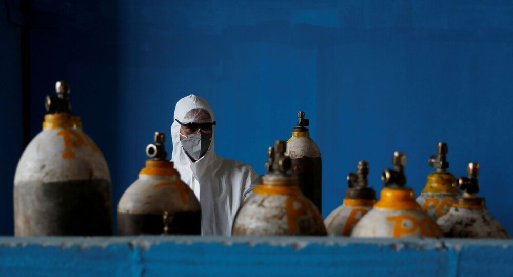 A medical worker stands next to an oxygen cylinder at the Yatharth Hospital in Noida, on the outskirts of New Delhi, India, September 15, 2020. Picture taken September 15, 2020.