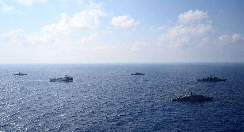 In this photo provided by the Turkish Defense Ministry, Turkey's research vessel, Oruc Reis, in red and white, is surrounded by Turkish navy vessels as it was heading to the west of Antalya in the Mediterranean, Turkey, Monday, 10 August 2020.