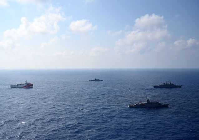 In this photo provided by the Turkish Defense Ministry, Turkey's research vessel, Oruc Reis, in red and white, is surrounded by Turkish navy vessels as it was heading in the west of Antalya on the Mediterranean, Turkey, Monday, Aug 10, 2020