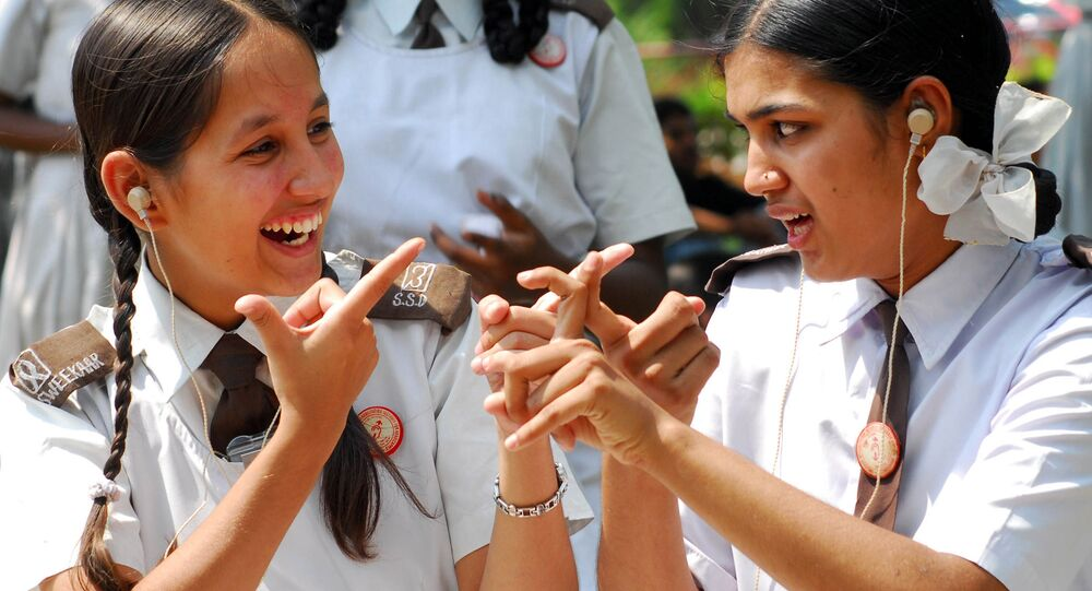 Hearing and speech impaired students Poonam Sharma, left, and Deepika interact with each other using sign language before an awareness rally for World Mental Health Week in Hyderabad, India, Saturday, Oct. 14, 2006