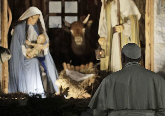 In this Dec. 31, 2019 file photo, Pope Francis stops by the Nativity exposed in St. Peter's square after presiding over vespers of the Feast of St. Mary and Te Deum of Thanksgiving at year's end, in St. Peter's Basilica at the Vatican.