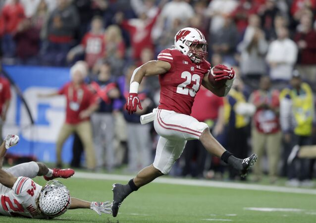 FILE - In this Dec. 7, 2019, file photo, Wisconsin running back Jonathan Taylor (23) runs for a touchdown past Ohio State cornerback Shaun Wade (24) during the first half of the Big Ten championship NCAA college football game, in Indianapolis. Taylor was selected to The Associated Press All-Big Ten Conference team, Wednesday, Dec. 11, 2019. (AP Photo/Michael Conroy, File)