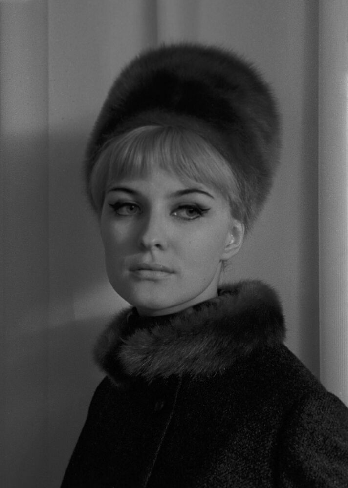 A model wears a coat with a fur collar and a fur hat, 1965