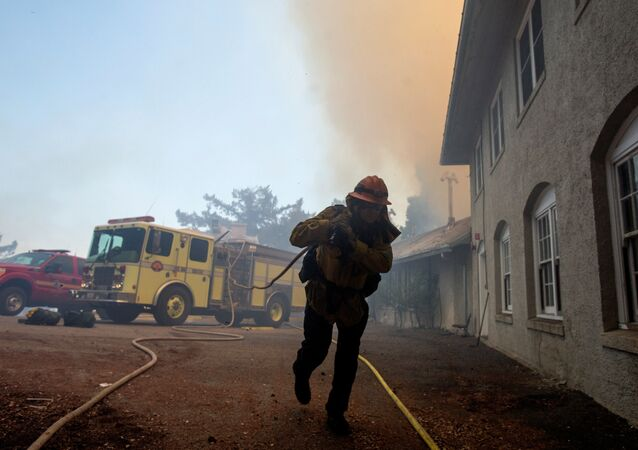 A firefighter carries a hose while defending the Mount Wilson observatory during the Bobcat Fire in Los Angeles, California, U.S., 17 September 2020.