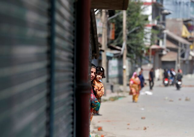 A Kashmiri woman holds a girl as they watch a protest after a gun battle between suspected militants and Indian security forces in Srinagar