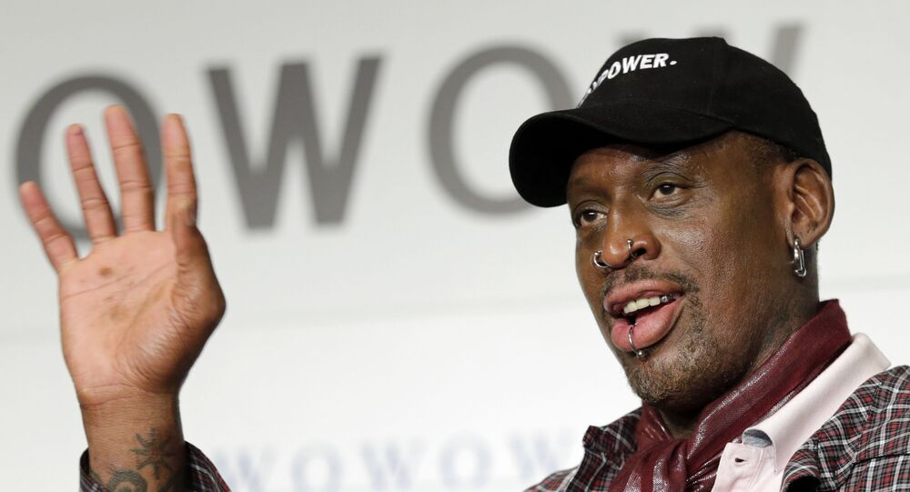 In this 25 October 2013, file photo, former basketball player Dennis Rodman waves during a news conference to promote a Japanese cable network's coverage of the upcoming NBA season in Tokyo.