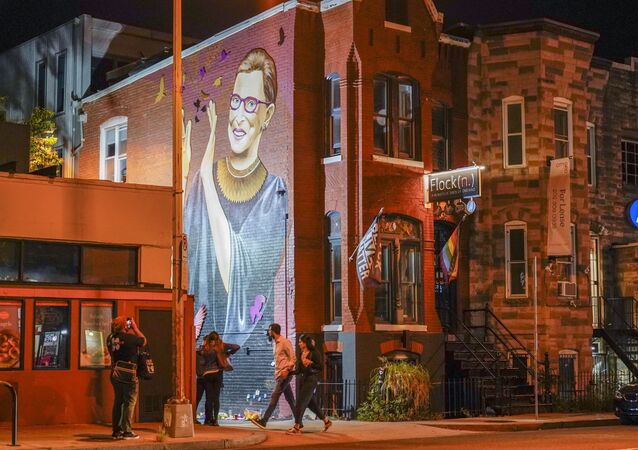 People gather under a mural of Supreme Court Justice Ruth Bader Ginsburg in the U Street neighborhood in Washington, Friday, 18 September 2020, after the announcement that Ginsburg died of metastatic pancreatic cancer at age 87