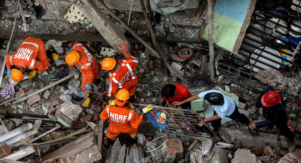 National Disaster Response Force (NDRF) officials and firemen remove debris as they look for survivors after a three-storey residential building collapsed in Bhiwandi on the outskirts of Mumbai, India, September 21, 2020.