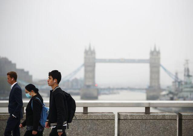 Commuters walk across the London Bridge