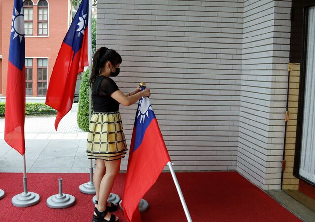 A staff member collects Taiwan flags outside of the Legislative Yuan in Taipei, Taiwan September 1