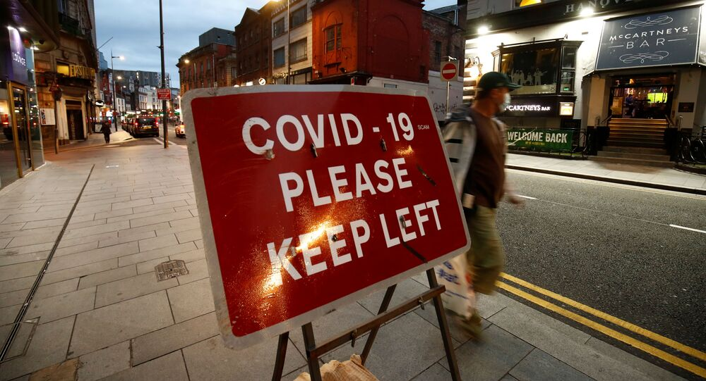 A man walks past a signage in Liverpool City Centre as Merseyside remains under lockdown due to the coronavirus disease (COVID-19) outbreak, in Liverpool, Britain September 22, 2020