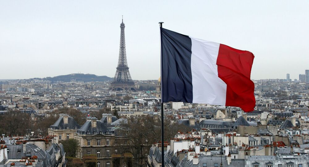 A city view shows the French flag above the skyline of the French capital as the Eiffel Tower and roof tops are seen in Paris, France, March 30, 2016.
