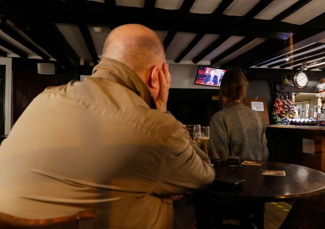 People watch the TV as Britain's Prime Minister Boris Johnson addresses the nation in The White Hart pub in Hemel Hempstead, Britain, 22 September 2020. REUTERS/Paul Childs