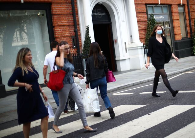 A woman wears a protective face mask as she walks on a street, amid the spread of the coronavirus disease (COVID-19) in Chelsea, London, Britain September 22, 2020