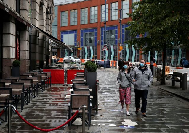 FILE PHOTO: People wearing protective masks walk as the city and surrounding areas face local restrictions in an effort to avoid a local lockdown being forced upon the region, amid the coronavirus disease (COVID-19) outbreak, in Manchester, Britain August 4, 2020