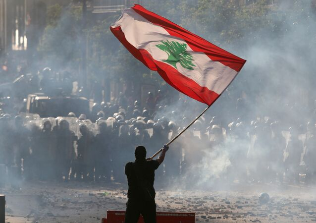 A demonstrator waves the Lebanese flag in front of riot police