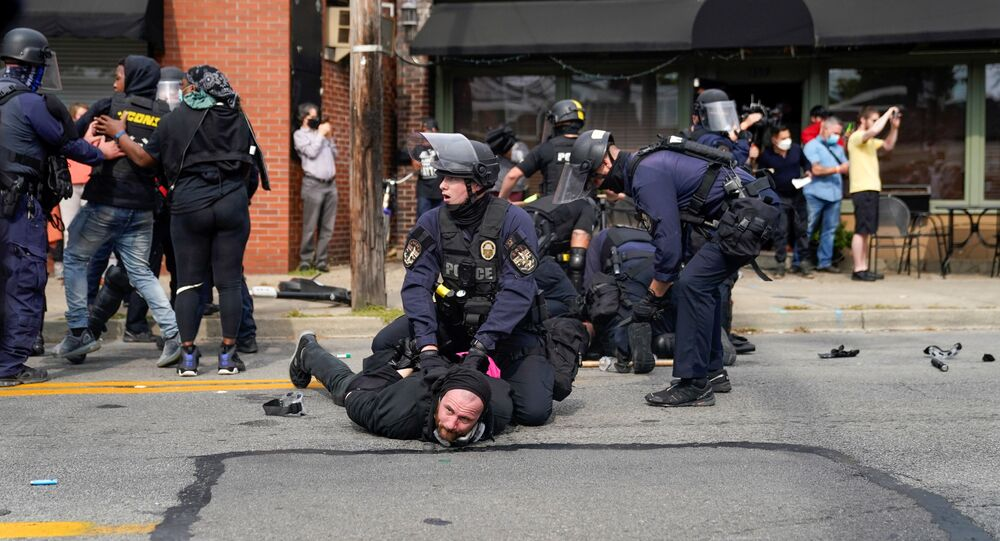 A police officer detains a protester as people react after a decision in the criminal case against police officers involved in the death of Breonna Taylor, who was shot dead by police in her apartment, in Louisville, Kentucky, U.S. September 23, 2020.
