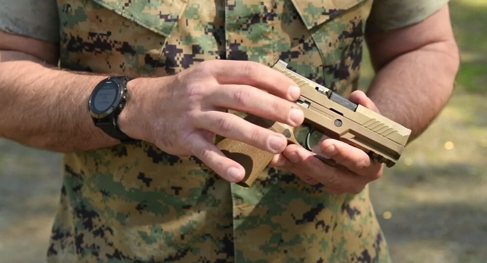 US military service member holds SIG Sauer M18 handgun.