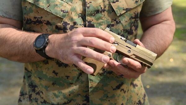 US military service member holds SIG Sauer M18 handgun. - Sputnik International