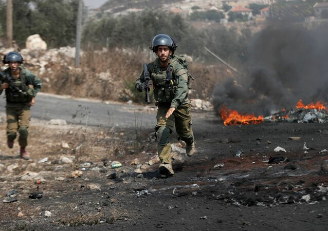 Israeli soldiers run towards demonstrators during a Palestinian protest against normalizing ties with Israel, in Kafr Qaddum town in the Israeli-occupied West Bank September 11, 2020