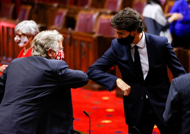 Canada's Prime Minister Justin Trudeau greets a Senator with an elbow-bump prior to the Throne Speech in the Senate, as parliament prepares to resume in Ottawa, Ontario, Canada September 23, 2020.