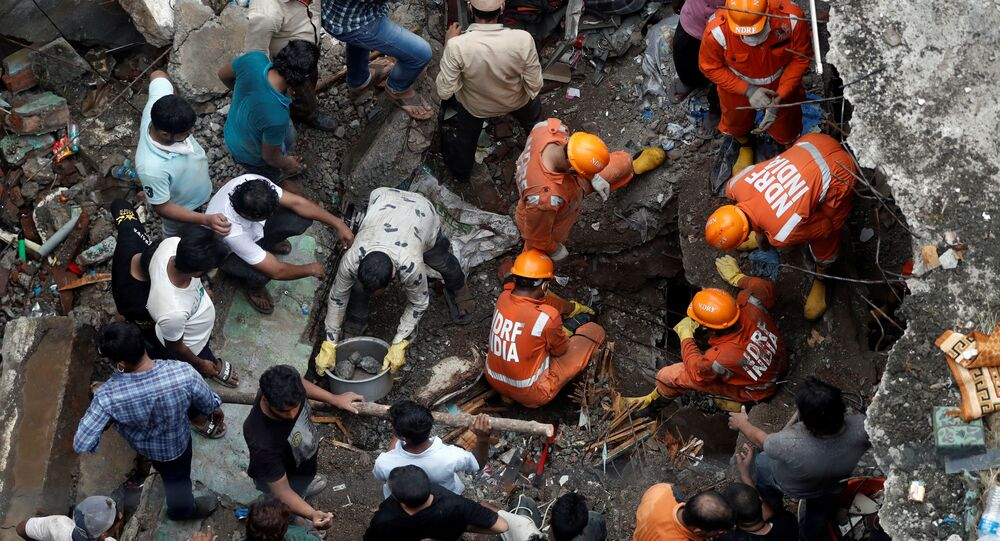 FILE PHOTO: National Disaster Response Force (NDRF) officials search for survivors as people help clear the rubble after a three-storey building collapsed in Bhiwandi, on the outskirts of Mumbai, India, September, 21 2020.
