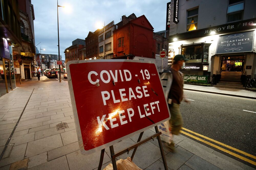 Liverpool, UK, has strict restrictions due to the spread of the coronavirus. In the photo - a passer-by in a mask walks along a deserted street.