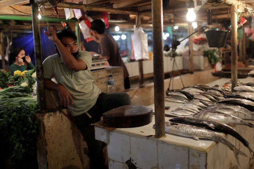 Bans and restrictions hit many areas of business. Both large companies and small ones suffered. Here you can see a sad masked seller awaits buyers at an empty fish market in Jakarta, Indonesia.