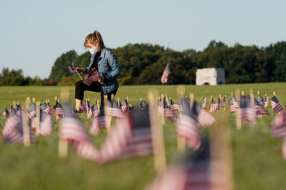 A young masked girl places United States flags in memory of those killed by COVID-19 on the National Mall in Washington. In the United States, the death toll from coronavirus has exceeded 200 thousand people.