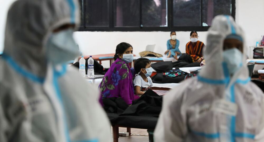 A woman sits with her child inside a quarantine centre for the coronavirus disease (COVID-19) patients amidst the spread of the disease at an indoor sports complex in New Delhi, India, September 22, 2020