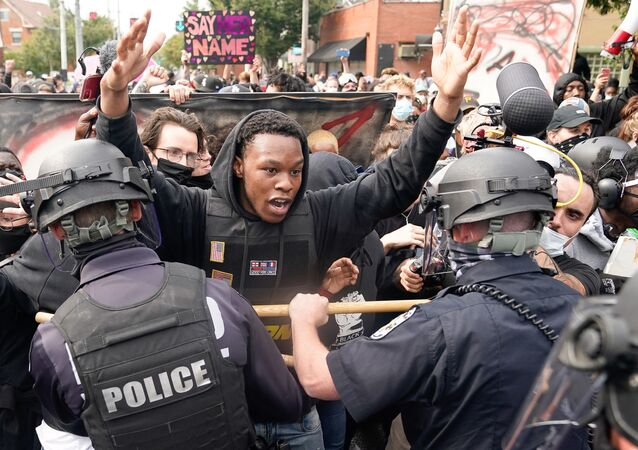 A protester clashes with police after a grand jury considering the March killing of Breonna Taylor, a Black medical worker, in her home in Louisville, Kentucky, voted to indict one of three white police officers for wanton endangerment, in Louisville, Kentucky, U.S. September 23, 2020.