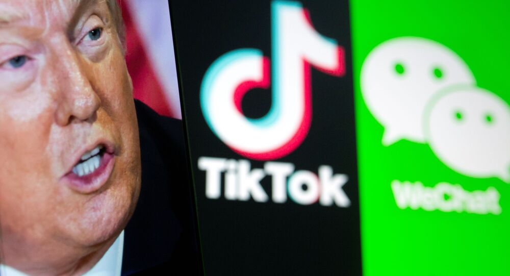 A picture of U.S. President Donald Trump is seen on a smartphone in front of displayed Tik Tok and WeChat logos in this illustration taken September 18, 2020.