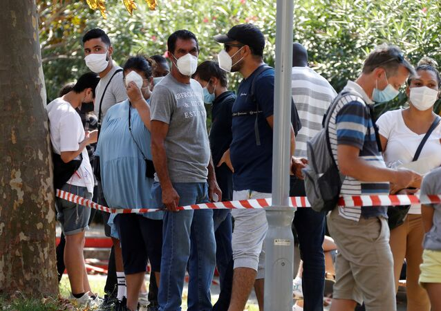 People wearing protective face masks wait in line at a testing site for coronavirus disease (COVID-19) in Marseille, France, September 17, 2020.