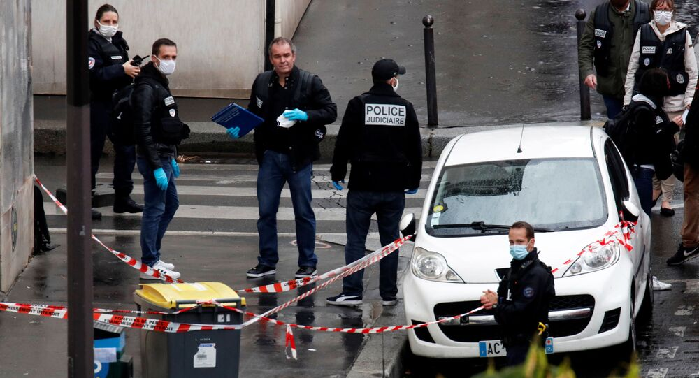 Police officers investigate the scene of an incident near the former offices of French magazine Charlie Hebdo, in Paris, France September 25, 2020