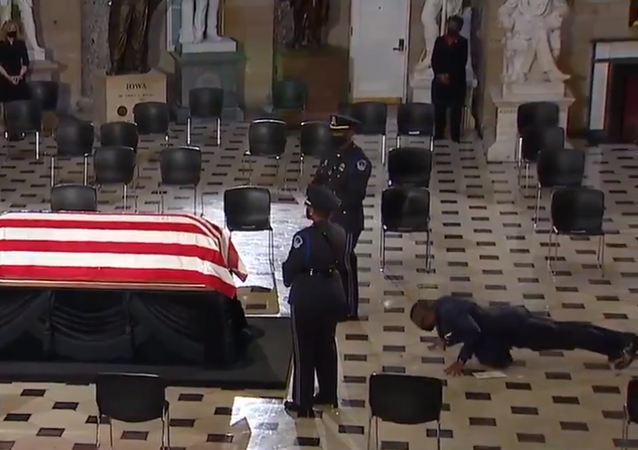 Screenshot from a video showing personal trainer of Justice Ruth Bader Ginsburg doint push-ups in her memory while standing in front of her casket during the memorial service in US Capitol