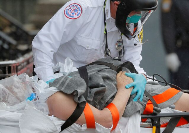 Boston EMS medics work to resuscitate a patient on the way to the ambulance amid the coronavirus disease (COVID-19) outbreak in Boston, Massachusetts, U.S., April 27, 2020.