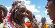 Maasai women decorate each other as they prepare to watch Maasai morans, or warriors, take part in an Olng'esherr ceremony at the foot of the Maparasha Hills, near Kajiado, in Kenya Wednesday, 23 September 2020. The Olng'esherr ceremony, which attracted more than 10,000 Maasai from around the region, is a meat-eating rite of passage which takes place only once every 10 nyears and marks the end of being a young warrior and the beginning of becoming an elder.