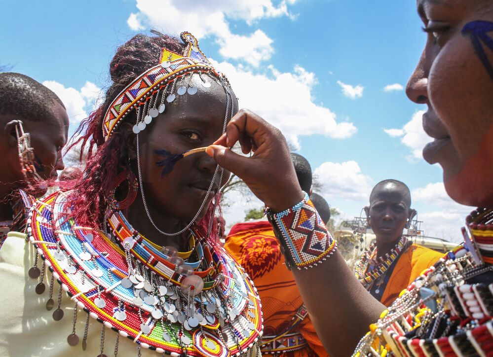 Maasai women decorate each other as they prepare to watch Maasai morans, or warriors, take part in an Olng'esherr ceremony at the foot of the Maparasha Hills, near Kajiado, in Kenya Wednesday, 23 September 2020. The Olng'esherr ceremony, which attracted more than ten thousand Maasai from around the region, is a meat-eating rite of passage which takes place only once every 15 years and marks the end of being a young warrior and the beginning of becoming an elder.