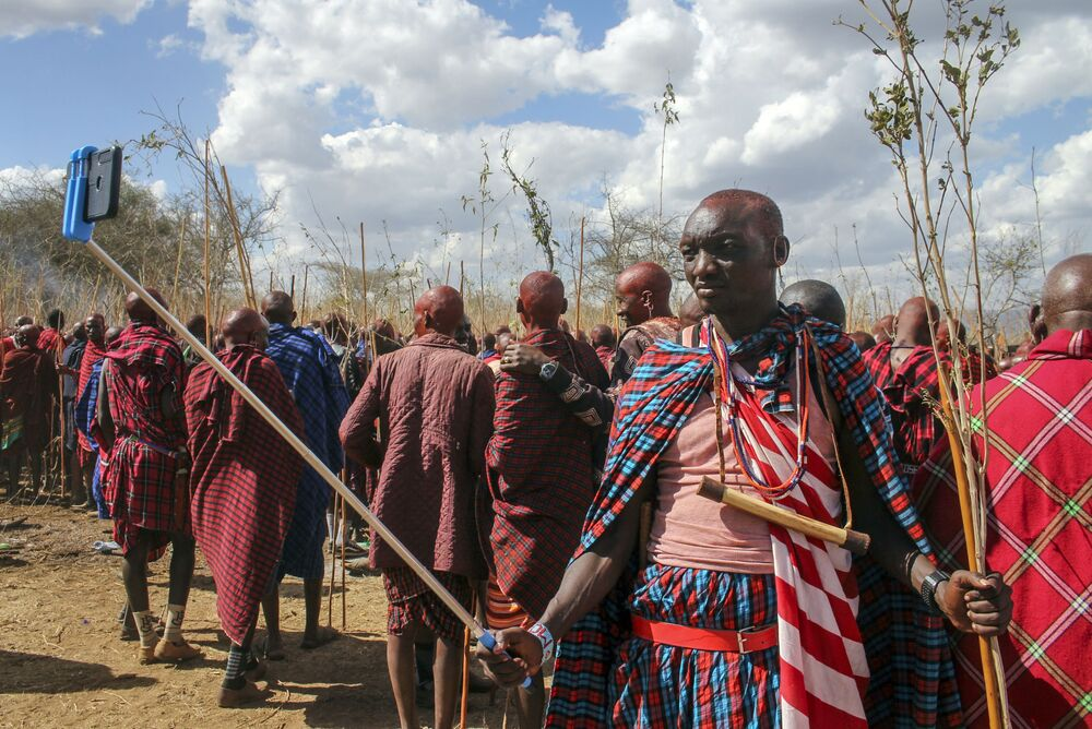 A Maasai moran, or warrior, takes a photograph with his smartphone using a selfie stick as he attends an Olng'esherr ceremony at the foot of the Maparasha Hills, near Kajiado, in Kenya Wednesday 23 September 2020. The Olng'esherr ceremony, which attracted more than ten thousand Maasai from around the region, is a meat-eating rite of passage which takes place only once every 15 years and marks the end of being a young warrior and the beginning of becoming an elder.