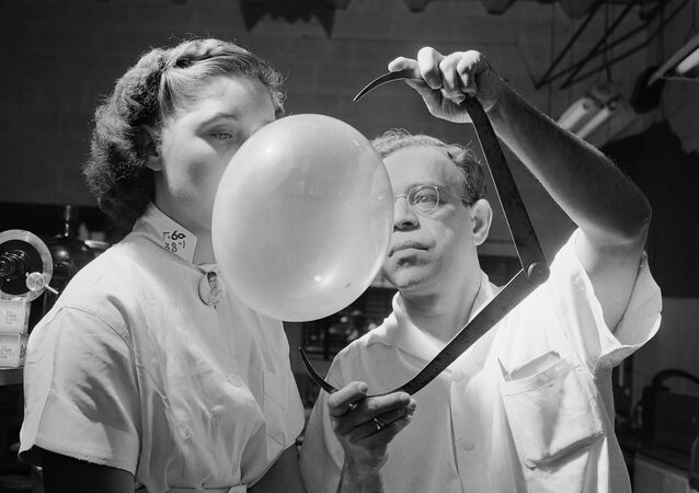 Dr. Morris Nafash, research director for the Bazooka Bubble Gum Company, whose job it was to test the texture and elasticity of the gum and to develop new flavors, is pictured measuring with an outside caliper a bubble blown by Josephine Zack on 16 September 1949 in New York.  Brooklyn-born Dr. Nafash came to his post after 11 years as a researcher at Columbia University's department of chemical engineering.  He blew about 100 bubbles a day and thinks kids probably won't ever blow bubbles much bigger than at present because the kid's face gets in the way.