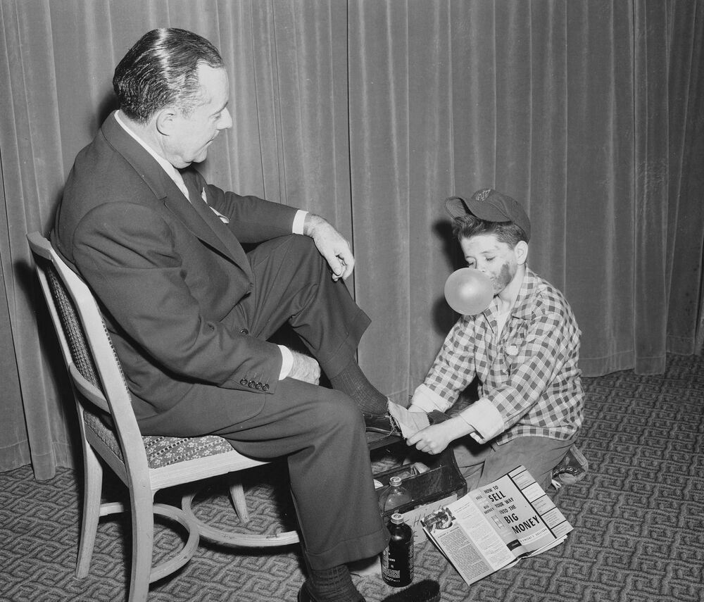 Raymond Duke a shoeshine boy, blows a bubble from his gum as he shines shoes of Walter T. Shirley, former New York City Commissioner of Commerce, 18 October 1954.