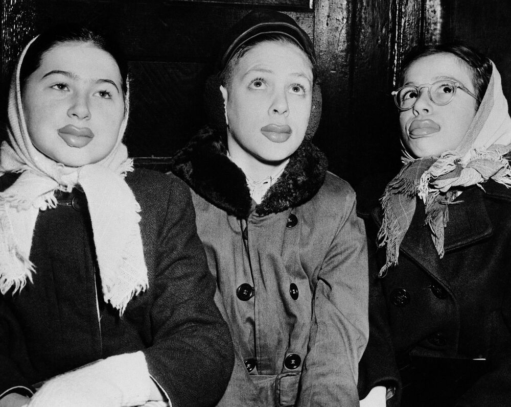 Latest craze in these parts among youngsters is false lips of chewing gum. Once the lips soften and become difficult to wear, the kids chew them for bubble gum. The exotic trio (left to right): Natalie Kozadoy, 13; Vincent Riggio, 11; and Evelyn Bondurc, 12, in Newark, N.J., shown 21 February 1947.