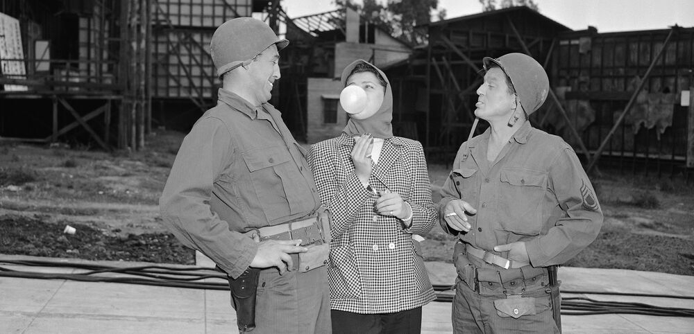 Robert Mitchum's secretary, Reva Frederick, teaches Charles McGraw (right) how to get full-sized results from a piece of bubble gum for the McGraw's role as a bubble gum expert in a scene for The Korean Story. Mitchum, seen here 28 January1952, seems to be duly impressed as he kids McGraw on the size of his bubbles.