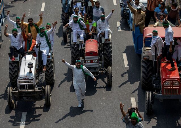 Farmers on tractors shout slogans as they arrive to block the Delhi-Uttar Pradesh border during a protest against farm bills passed by India's parliament