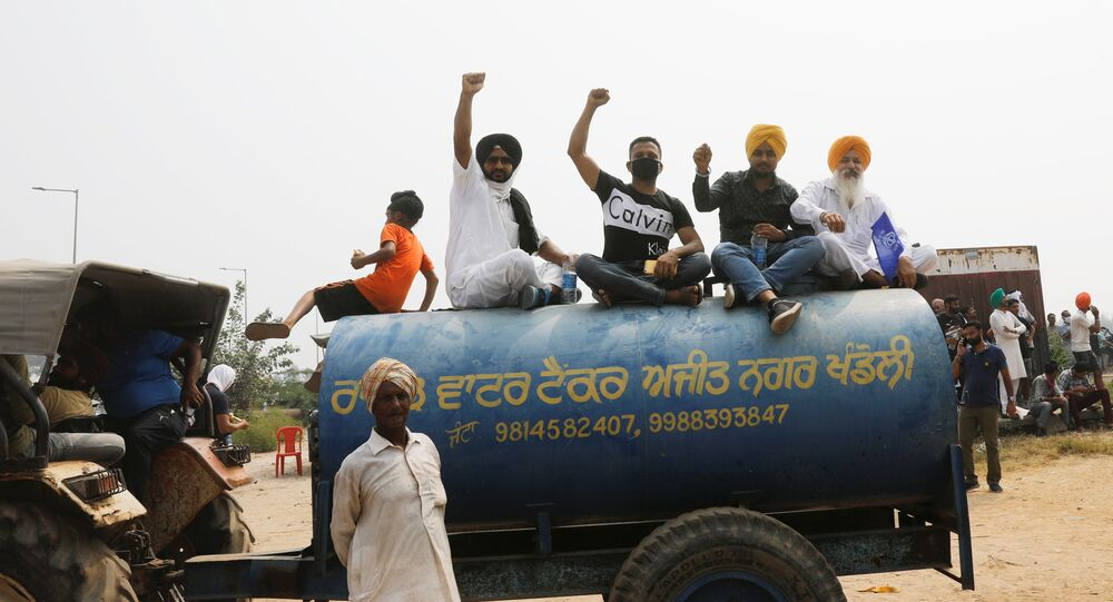 Farmers sit on the water tank as they block a national highway during a protest against farm bills passed by India's parliament