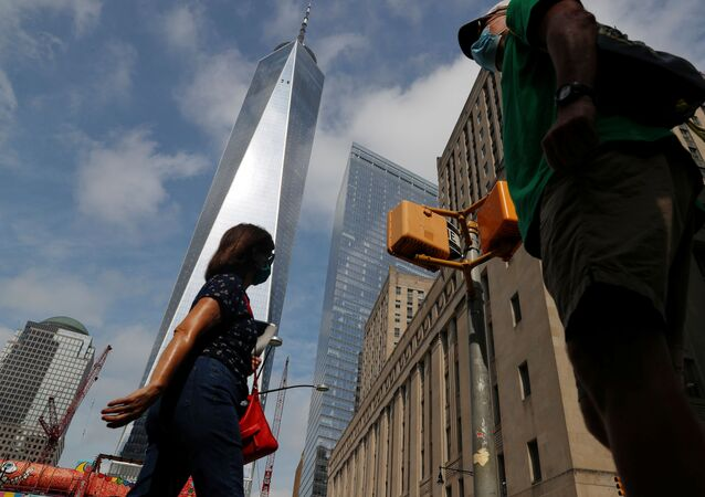 People wearing protective face masks walk by One World Trade Center two days before the 19th anniversary of the 9/11 attacks, amid the coronavirus disease (COVID-19) pandemic, in the lower section Manhattan, New York City, U.S., September 9, 2020.