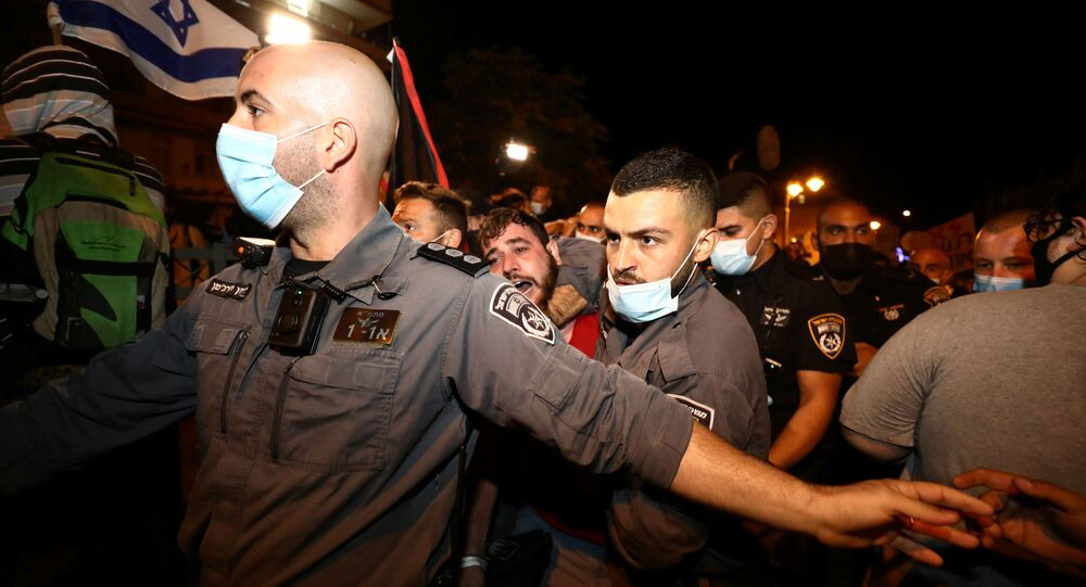 Police detain a protestor during a protest against Israeli Prime Minister Benjamin Netanyahu's alleged corruption and economic hardship stemming from lockdown, after Israel entered a second nationwide lockdown amid a resurgence in the new coronavirus disease (COVID-19) cases, in Jerusalem, September 26, 2020.