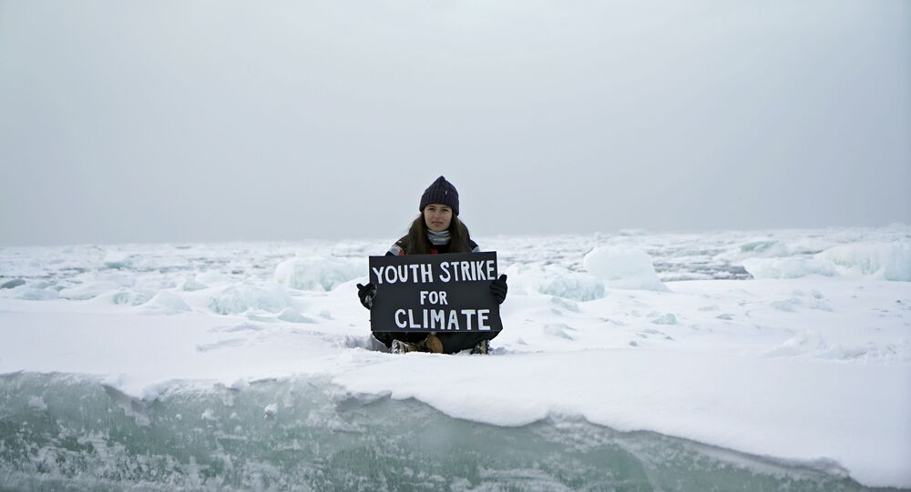 Environmental activist and campaigner Mya-Rose Craig, 18, holds a cardboard sign reading youth strike for climate as she sits on the ice floe in the middle of the Arctic Ocean, hundreds of miles above the Arctic Circle, 20 September 2020.