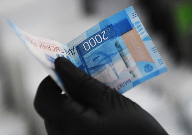 A buyer holds a 2,000-ruble note