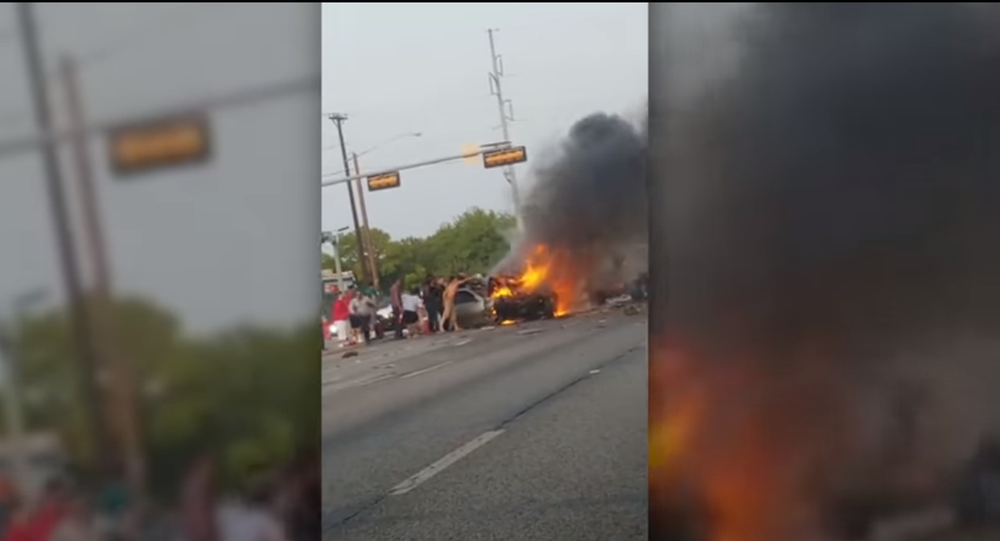 Screenshot of the video showing a fiery incident involving multiple vehicles in Dallas, where the police officers, with the help of the community members, saved an unconscious man from a burning car